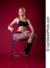young woman posing in dance sport costume on chair -...