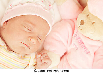 Cute little baby sleeping in pink pajama with teddy bear toy