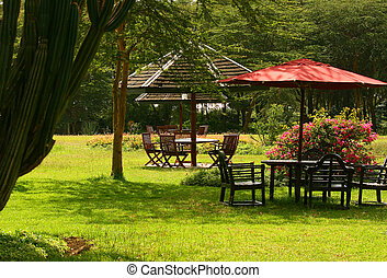 Outdoor summertime cafeteria surrounded by gardens and...