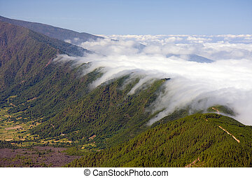Clouds falling over the mountain ridge of La Palma, Canary...