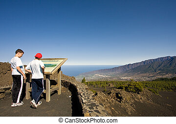 Two boys looking at a map at La Palma, Canary Islands