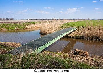 farmland with pedestrian bridge crossing a wide ditch -...