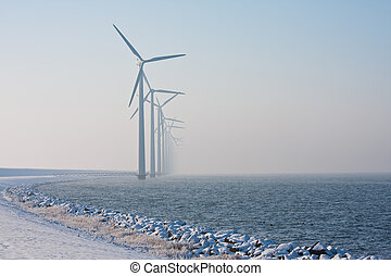 Row of Dutch windmills disappearing in winter haze