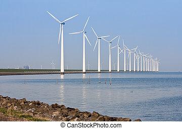 Windmills along the coastline, mirroring in the calm sea. -...