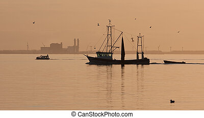 Fishing ship sailing home in sunset