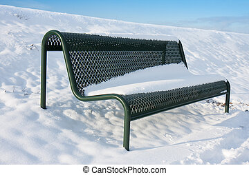 Green iron bench covered by snow in wintertime