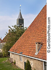Old dutch historic farmhouse with churchtower behind it