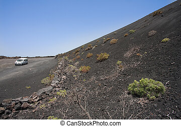Road with car beside enormous volcanic ashes mountain at La Palma, Canary Islands