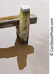 Old weathered bollard with a reflection in the water