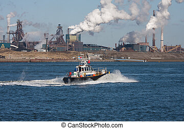 Dutch steel factory along the coast with motorboat in front