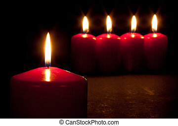 Set of red candles burning in the dark