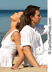Young couple sitting on a seacoast back to back
