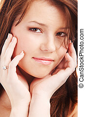 Closeup portrait of a young woman touching her face