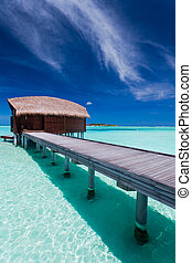 Overwater bungalow in lagoon around tropical island -...