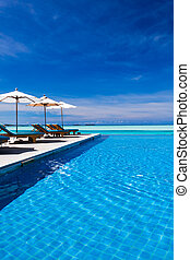 Deck chairs and infinity pool over amazing lagoon - Deck...