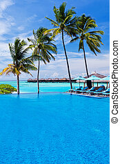 Infinity pool with umbrellas and palm trees over lagoon -...