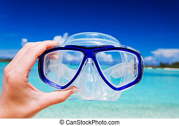Snorkel googles against beach and sky - Hand holding snorkel...