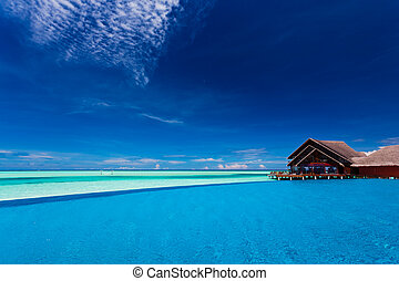 Infinity pool over tropical lagoon with clear blue sky -...