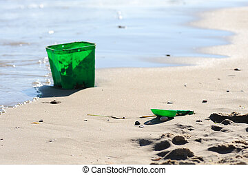 Green bucket and spade disgarded on beach