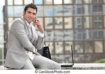 Businessman talking on phone in front of a laptop computer