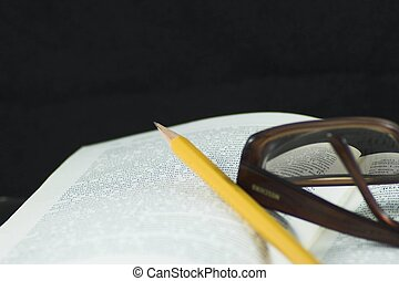 Pencil and glasses on a book - Students Studying a book -...