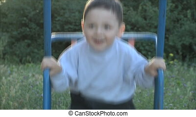 little boy riding on a swing 1