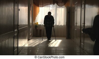 man goes to the hospital corridor on the crutches