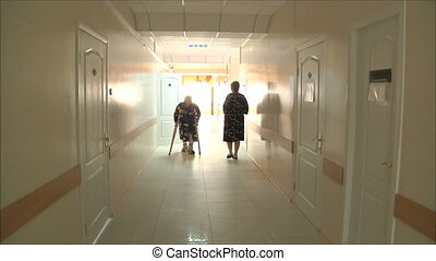 woman goes to the hospital corridor on the crutches