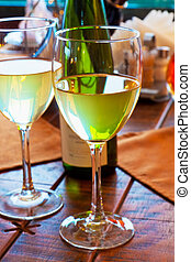 Two goblets with white wine on restaurant table - Macro view...