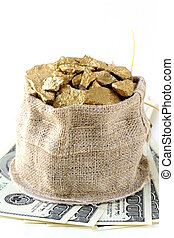 Gold nuggets placed on top of a hundred dollar bill
