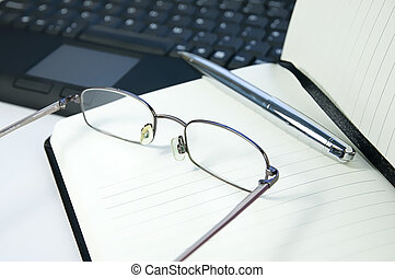reading glasses and pen on notebook with keyboard