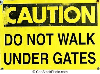 CAUTION SIGN - A caution sign with black lettering against a...