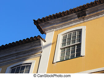 Old yellow house - Old colonial windows, roof tiles and blue...