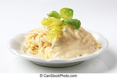 Spaghetti with creamy sauce garnished with fresh basil