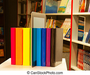 Row of colorful books and tablet PC reader in the book shop