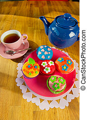 Colorful cupcakes by the tea at the sunny table