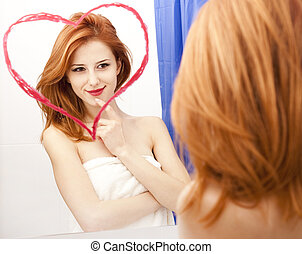 Redhead girl near mirror with heart at it in bathroom