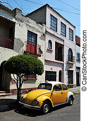 Mexico City Street Scene - A beetle car is parked next to a...