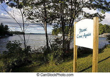 Sign overlooking calm lake water shot in Muskoka, Ontario...
