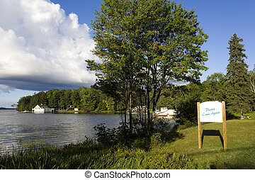 Sign overlooking calm lake water shot in Muskoka, Ontario Cottage Country