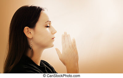 Woman Praying - A woman praying with her hands together on...