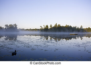 Calm lake water with mist shot in Muskoka, Ontario Cottage...