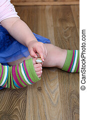 Toe ring - Little girl playing with a gold ring on her toe