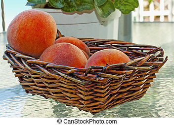 Peaches in a wooden basket, over a glass table