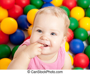 Portrait of a smiling infant sitting among colorful balls -...
