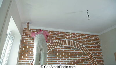 worker paints the ceiling