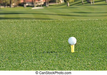 Golf ball sits on a tee ready to hit