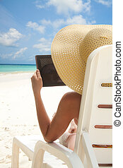 Woman sitting on the beach and browsing internet with tablet computer