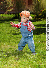 Toddler make first steps in the garden