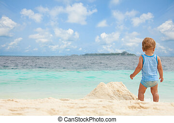 Kid, summer, beach sandbox - Toddler playing with sand on...